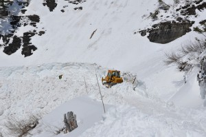 A bulldozer and avalanche spotter work together to plow a section of the road. Photo: Glacier National Park Flickr site