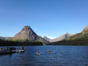 Two kayakers paddle on Two Medicine Lake.